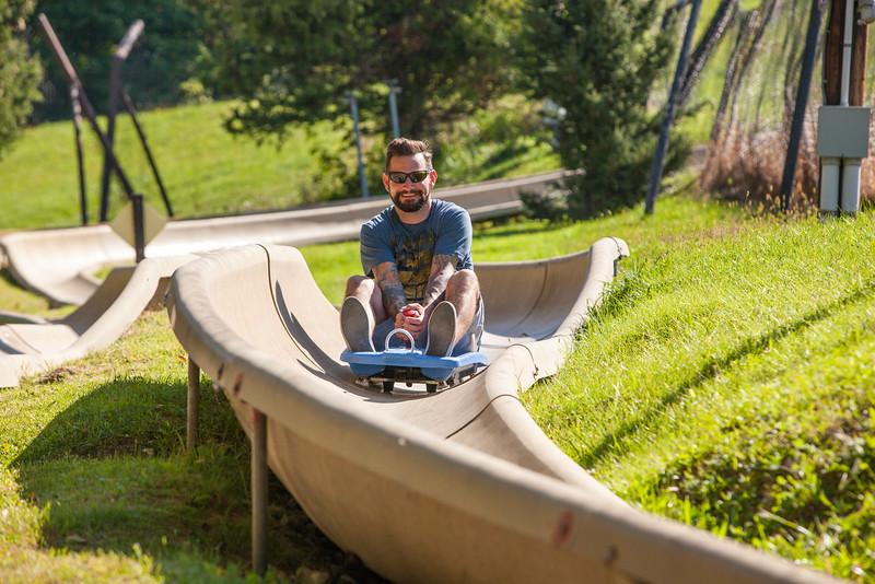 Man happily sliding down the Alpine Slide at Chestnut Mountain Resort